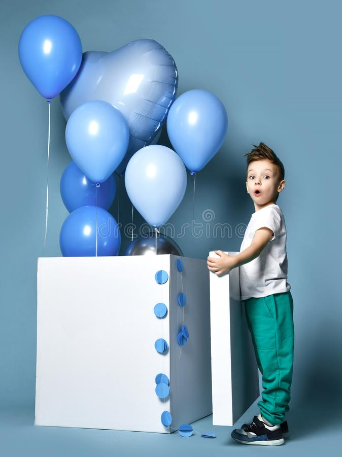 Happy little boy with pastel color blue balloons and empty white box for birthday party. With free text space stock images