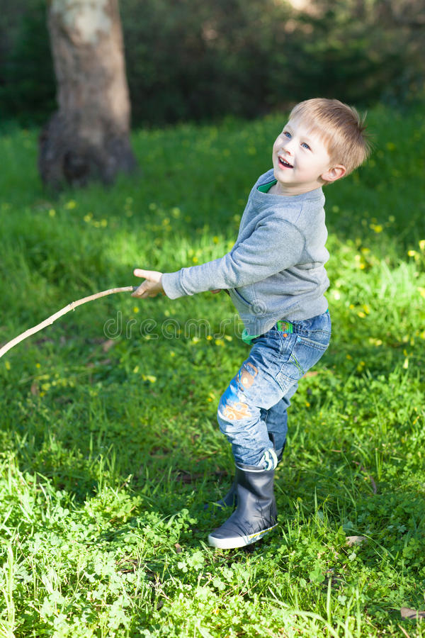 Happy little boy plaing with a stick in a park stock photos