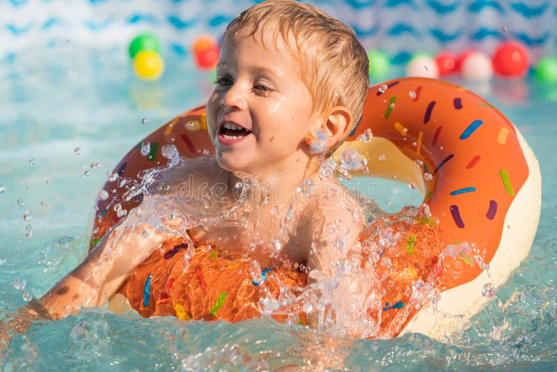 Happy little boy playing with colorful inflatable ring royalty free stock images