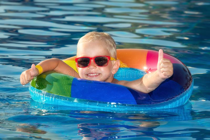 Happy little boy playing with colorful inflatable ring in outdoor swimming pool on hot summer day. Kids learn to swim. Child water royalty free stock images