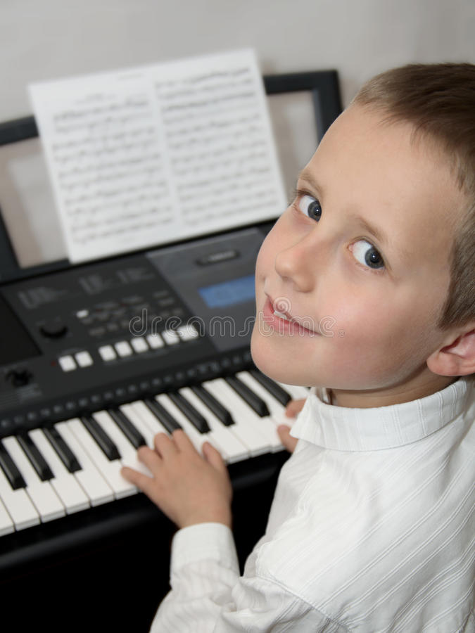 Happy little boy playing keyborad piano stock photos