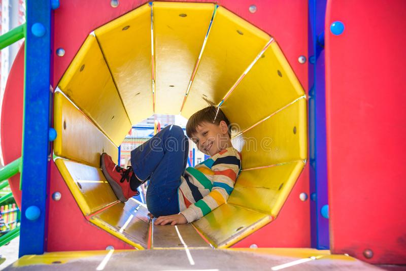 Happy little boy playing in tube or tunnel at the modern playground. Summer holidays. Happy and healthy childhood stock image