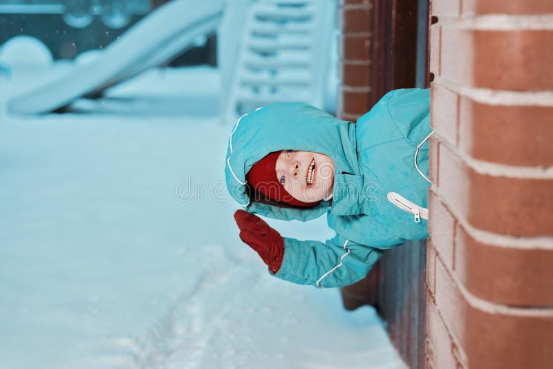 Happy little boy playing in winter. the child waves and smiles stock image