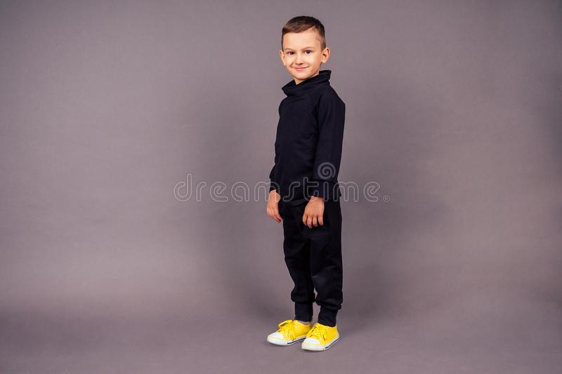 Happy little boy posing on a gray background in studio . male child model dressed black sporty suit and yellow sneakers. Sport Style royalty free stock photo