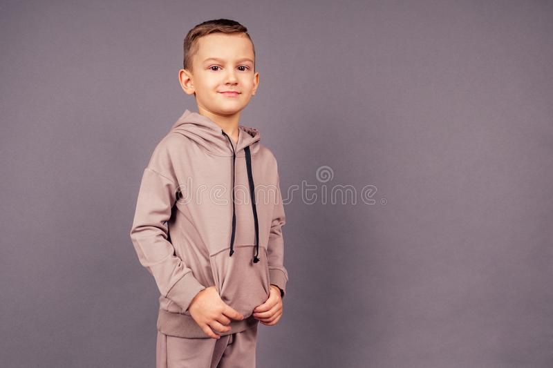 Happy little boy posing on a gray background in studio . male child model dressed sporty suit. Sport Style.  royalty free stock photos