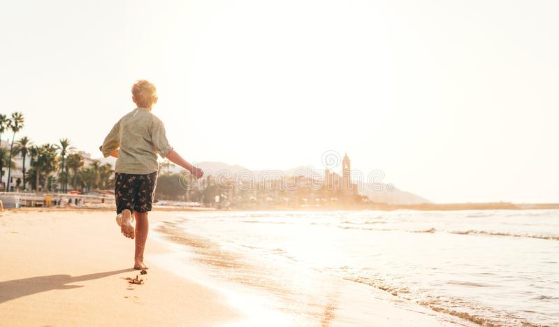 Happy little boy running by Mediterranean spain coast in Sitges town near Barcelona stock image