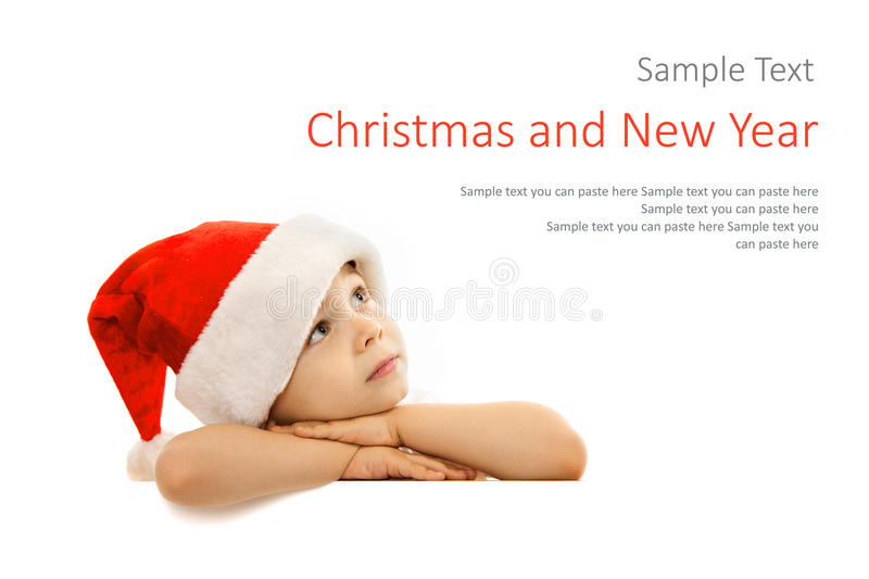 Happy little boy in Santa hat peeking from behind. Blank sign billboard. Isolated on white background. Space for Your Text. Sale, holidays, christmas, new year royalty free stock photos