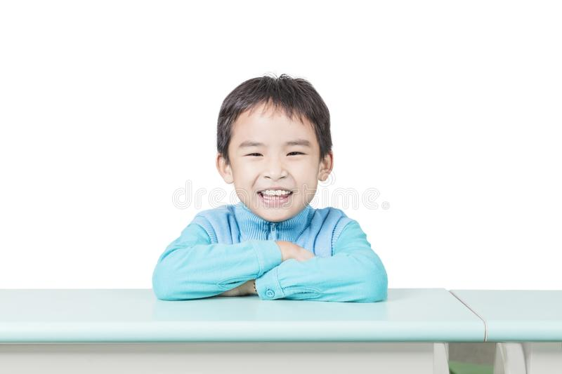Happy little boy sitting at desk in classroom royalty free stock photos