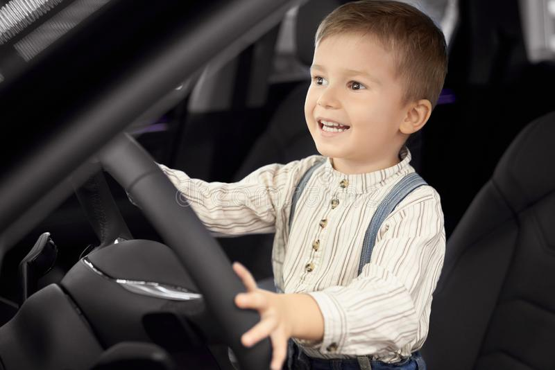 Happy little boy sitting in driver`s seat, smiling. stock photo