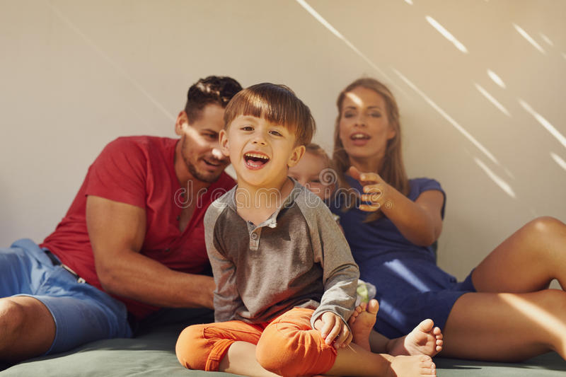 Happy little boy sitting on patio with his family stock image