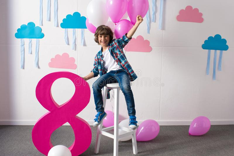 happy little boy sitting on stool with balloons and smiling at camera at birthday stock photography