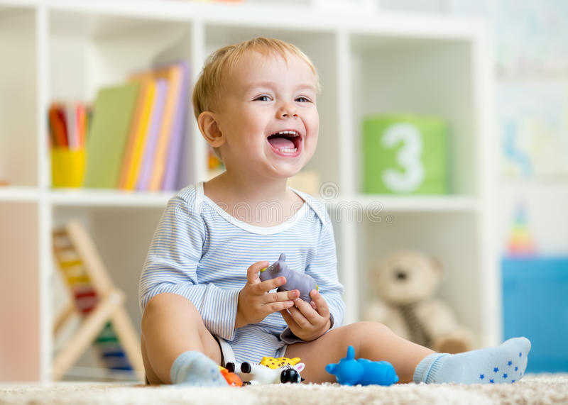 Happy little boy. Smiling child plays animal toys. Happy little boy. Smiling child toddler plays animal toys at home or kindergarten stock photography