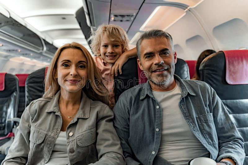 Happy little boy staying near mother and father in plane stock photo