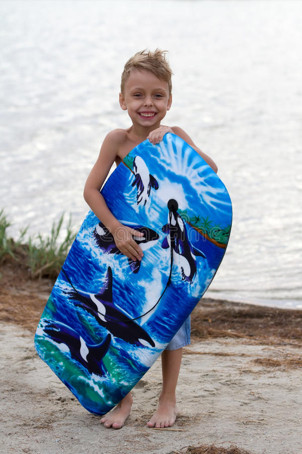 Happy little boy with surfing board royalty free stock photos