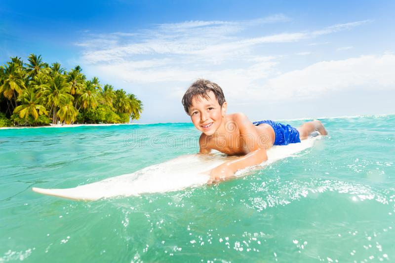 Happy little boy swim on surfing board in the sea. On his vacation with tropical island on background stock photography