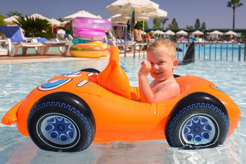 Happy little boy swimming in the inflatable car on summer holidays stock images