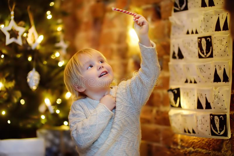 Happy little boy takes last sweet from advent calendar on Christmas eve. Traditional christmas calendar for kids royalty free stock image