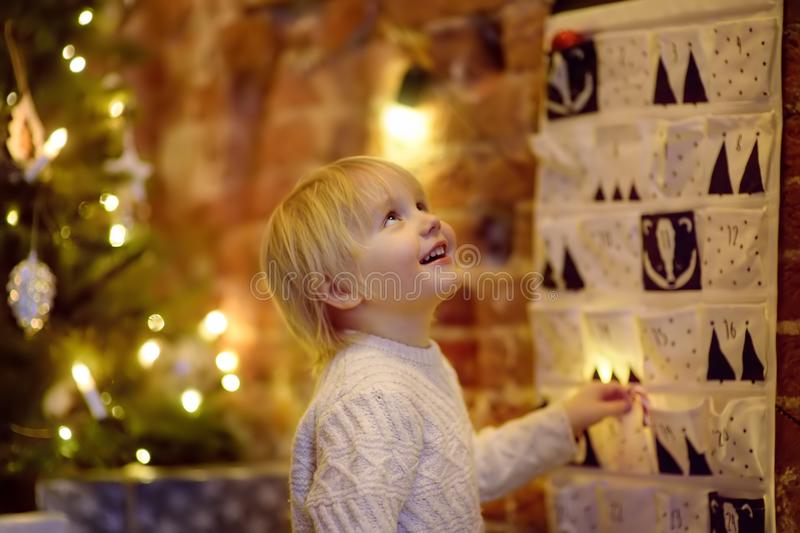 Happy little boy takes sweet from advent calendar on Christmas eve royalty free stock photography