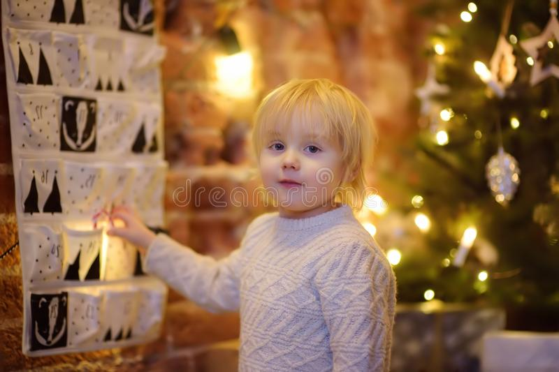 Happy little boy takes sweet from advent calendar on Christmas eve. Traditional christmas calendar for kids stock image