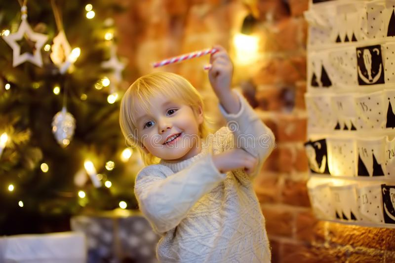 Happy little boy takes sweet from advent calendar on Christmas eve. Traditional christmas calendar for kids stock photography