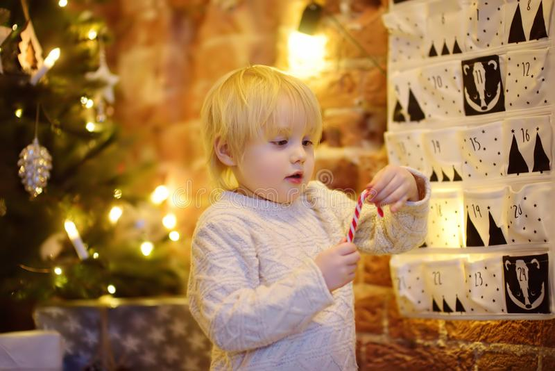 Happy little boy takes sweet from advent calendar on Christmas eve. Traditional christmas calendar for kids stock photo