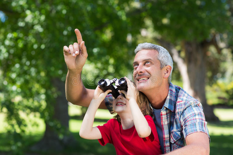 Happy little boy using binoculars with his father royalty free stock images