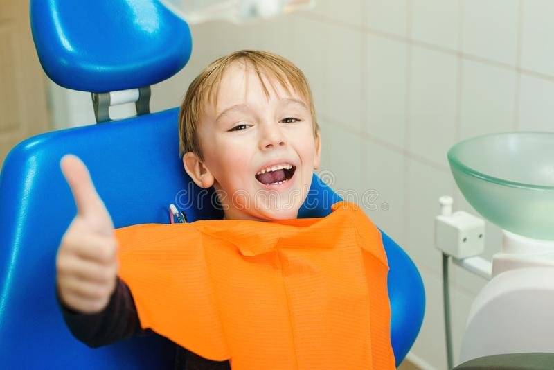 Happy little boy visiting dentist. Child sitting in a blue chair dental. Examining little boy`s teeth in dental clinic.  royalty free stock images