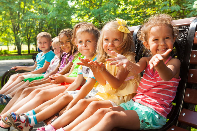 Happy little boys and girls on the bench in park royalty free stock image