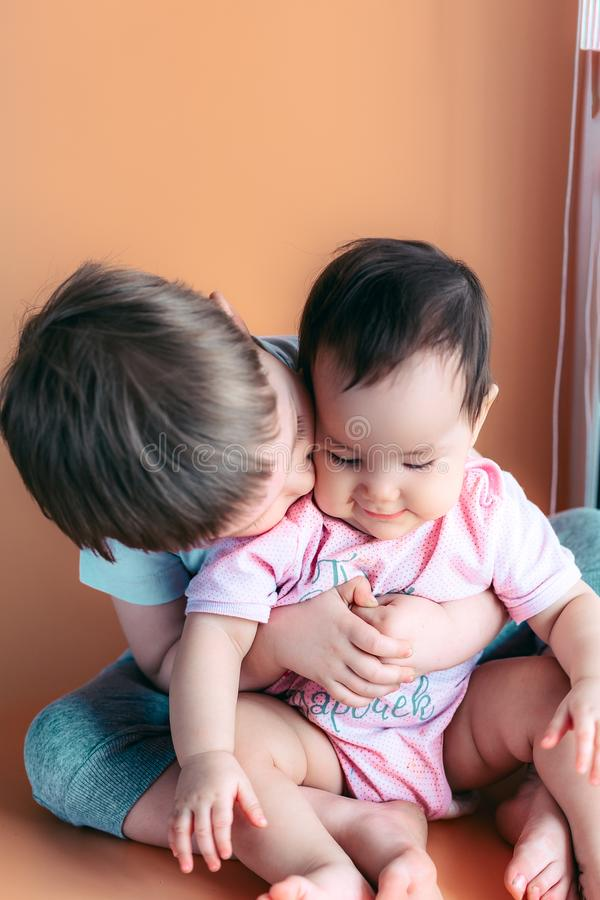 Happy little brother playing hugs his sister baby, boy and girl embraces kisses, concept love and parenting.  royalty free stock photos