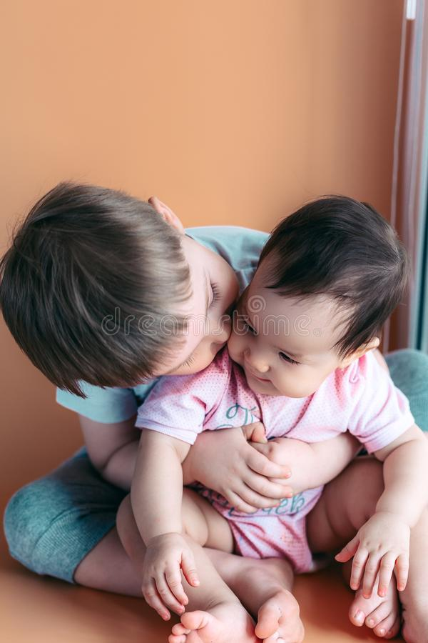 Happy little brother playing hugs his sister baby, boy and girl embraces kisses, concept love and parenting.  royalty free stock photography