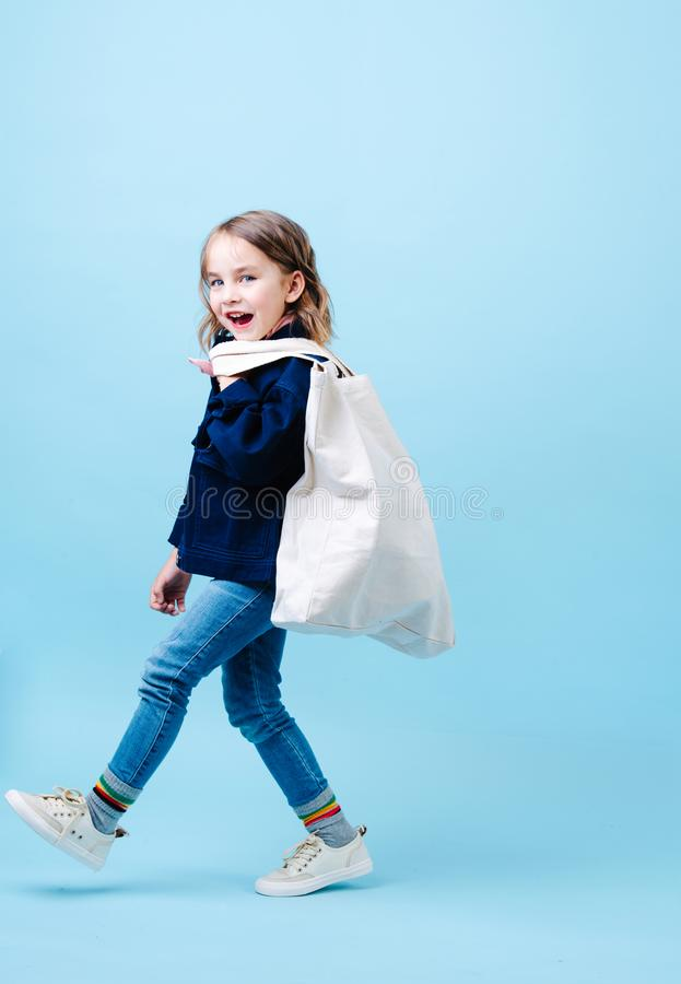 Happy little girl is walking along, holding eco bag stock images