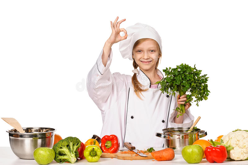 Happy little chef girl with parsley showing OK stock photo