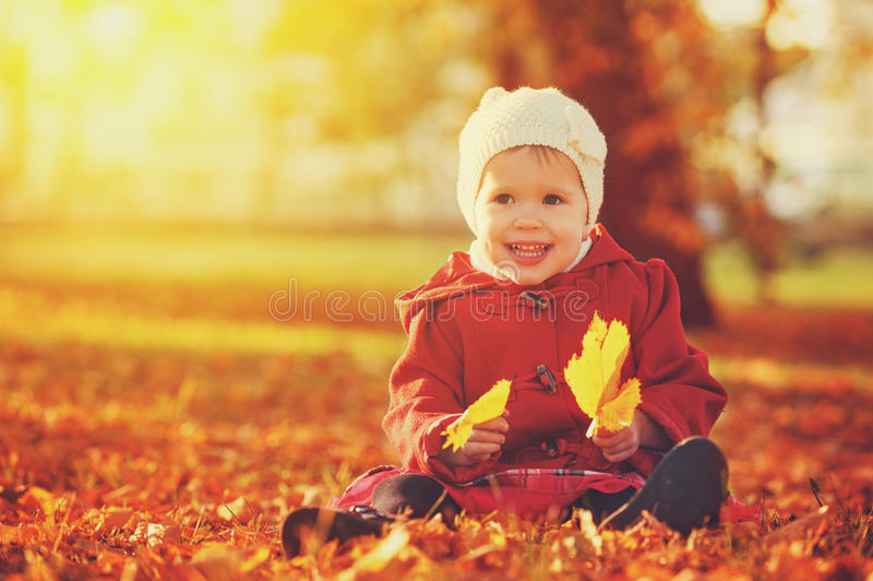 Happy little child, baby girl laughing and playing in autumn. Happy little child, baby girl laughing and playing in the autumn on the nature walk outdoors royalty free stock photos