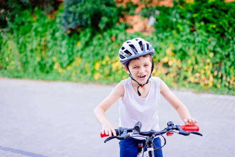Happy little child boy in white helmet on bicycle royalty free stock photos