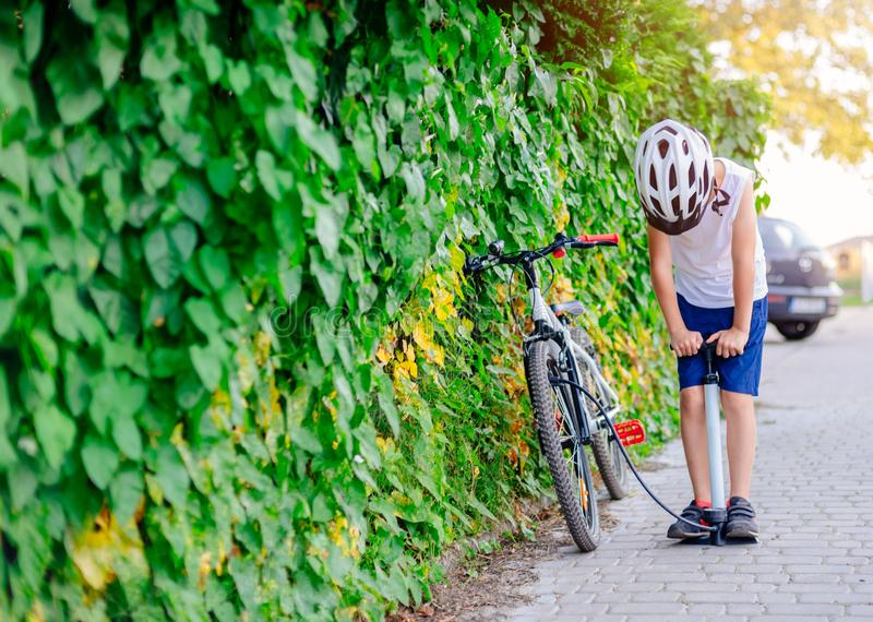 Happy little child boy in white helmet inflating tire in his bicycle stock photography