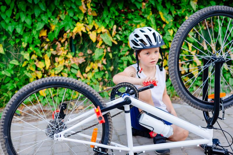 Happy little child boy in white helmet repairing his bicycle royalty free stock images