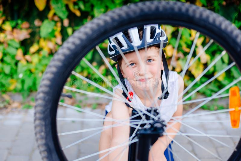 Happy little child boy in white helmet repairing his bicycle stock photography
