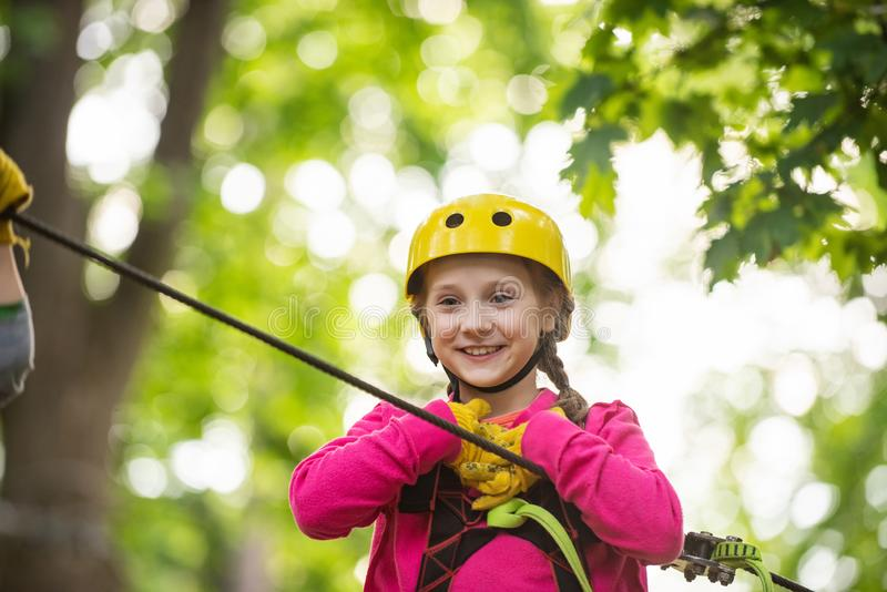 Happy little child climbing on a rope playground outdoor. Cute child in climbing safety equipment in a tree house or in. A rope park climbs the rope. Toddler royalty free stock images