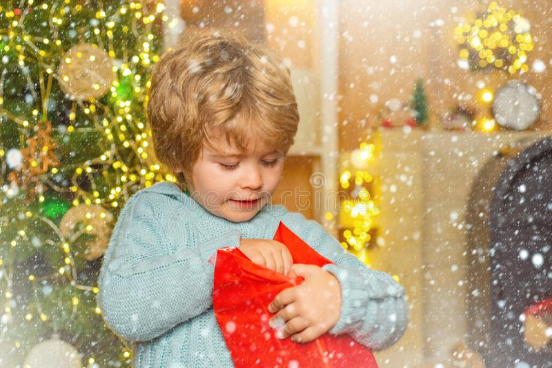 Happy little child dressed in winter clothing think about Santa near Christmas tree. Christmas kids - happiness concept stock photo