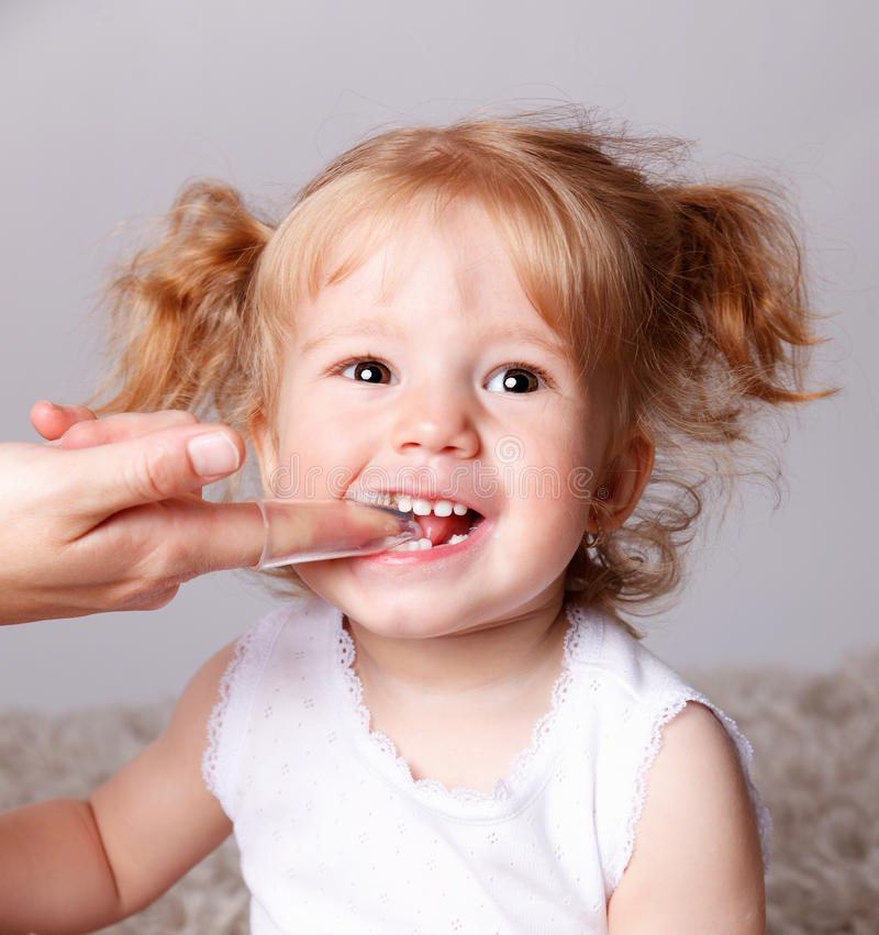 Happy little child getting her teeth brushed with finger toothbrush royalty free stock photo