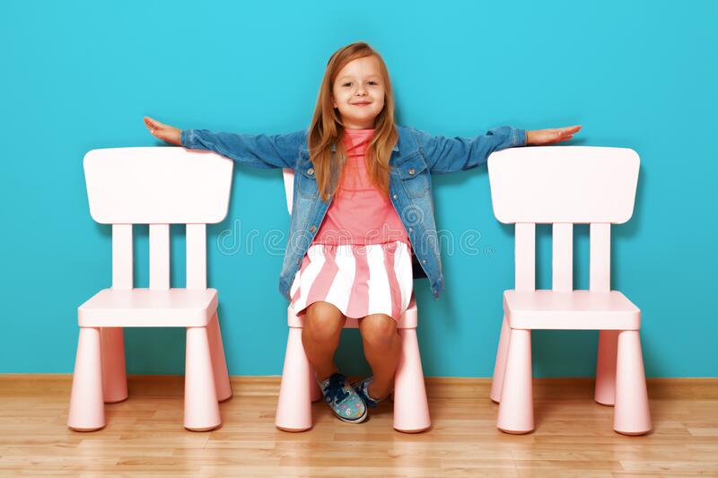 A happy little child girl with arms extended to the side sits on a chair against the background of a blue wall. royalty free stock photos