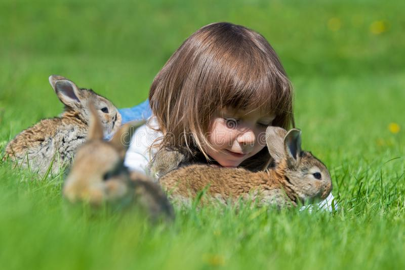 Happy little child girl with cute rabbit. Portrait of kid with pet. Outdoors. royalty free stock images