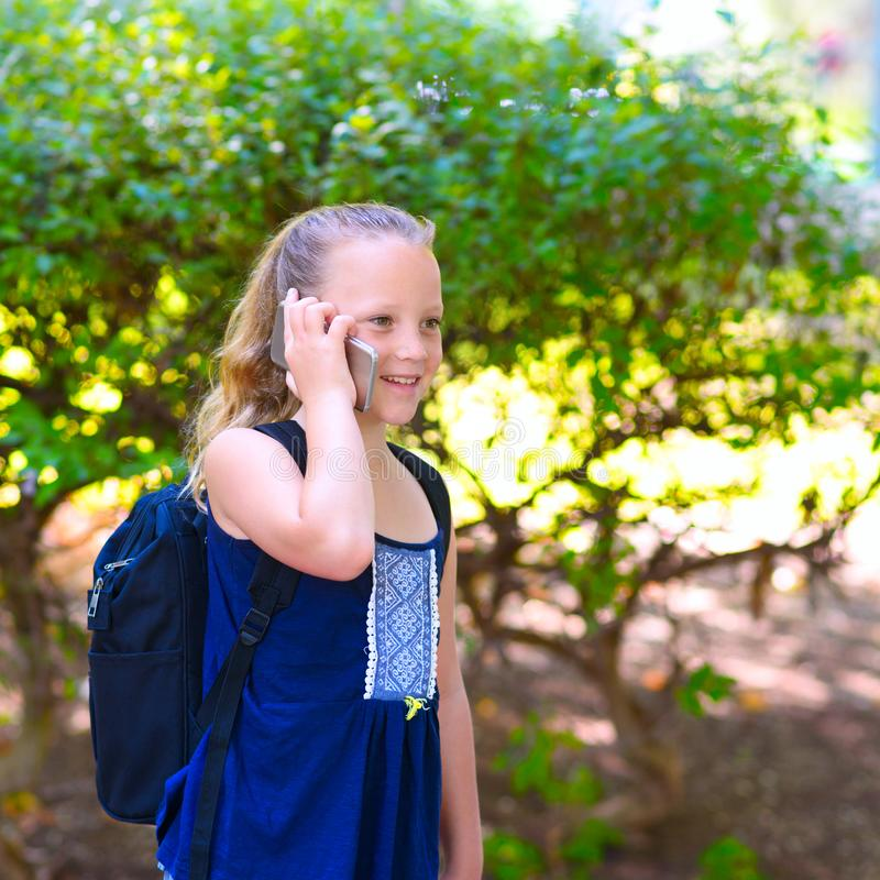 Happy little child girl go to school and talking on mobile phone at city park. royalty free stock photo