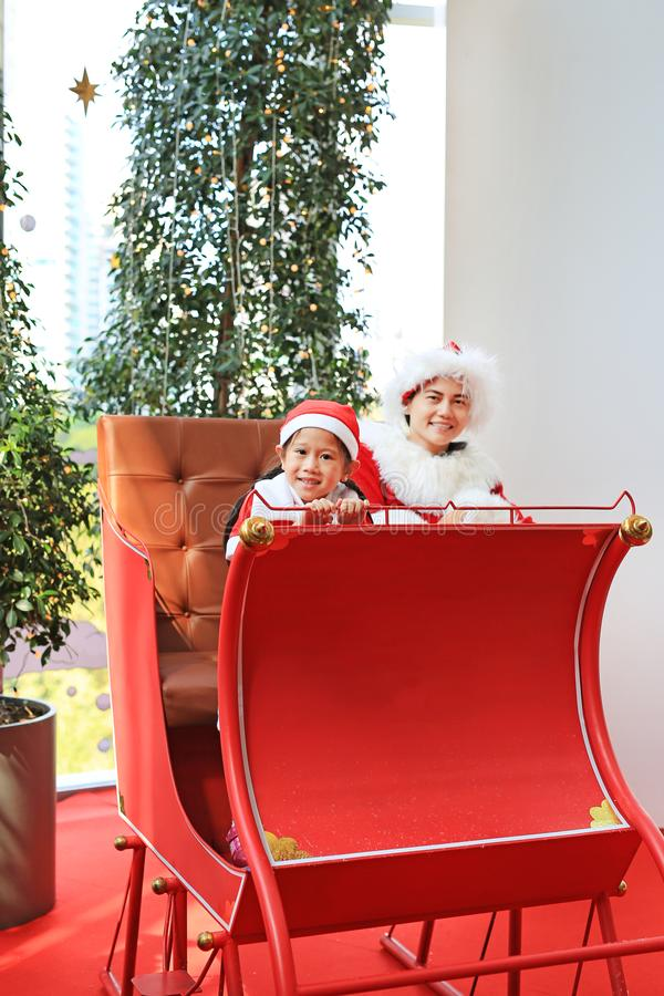 Happy little child girl and her mother in santa costume dress sitting on red sledge christmas background. Merry Christmas and. Happy new year royalty free stock photo
