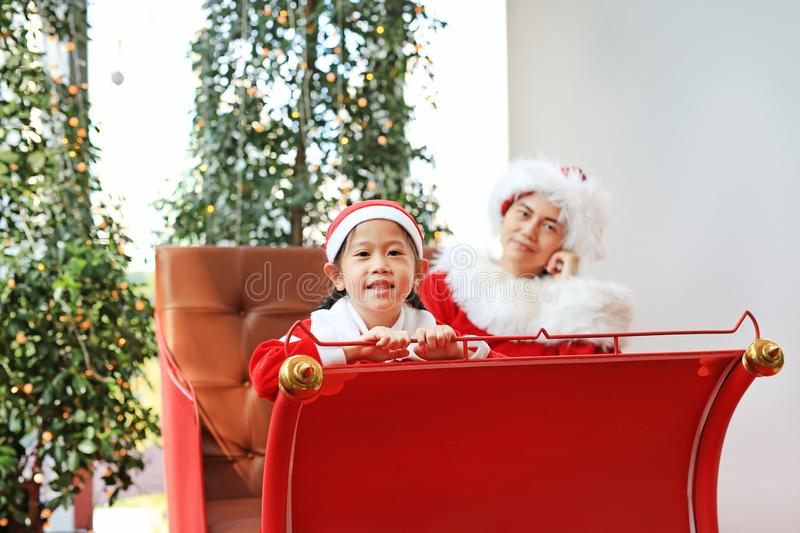 Happy little child girl and her mother in santa costume dress sitting on red sledge christmas background. Merry Christmas and. Happy new year stock photos
