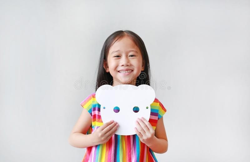 Happy little child girl holding blank white animal paper mask on her chest on white background. Idea and concept for kid dressed. Up playing animal face stock image