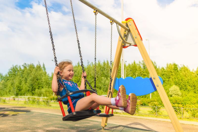 Happy little child girl laughing and swinging on a swing in the city park in summer royalty free stock photo