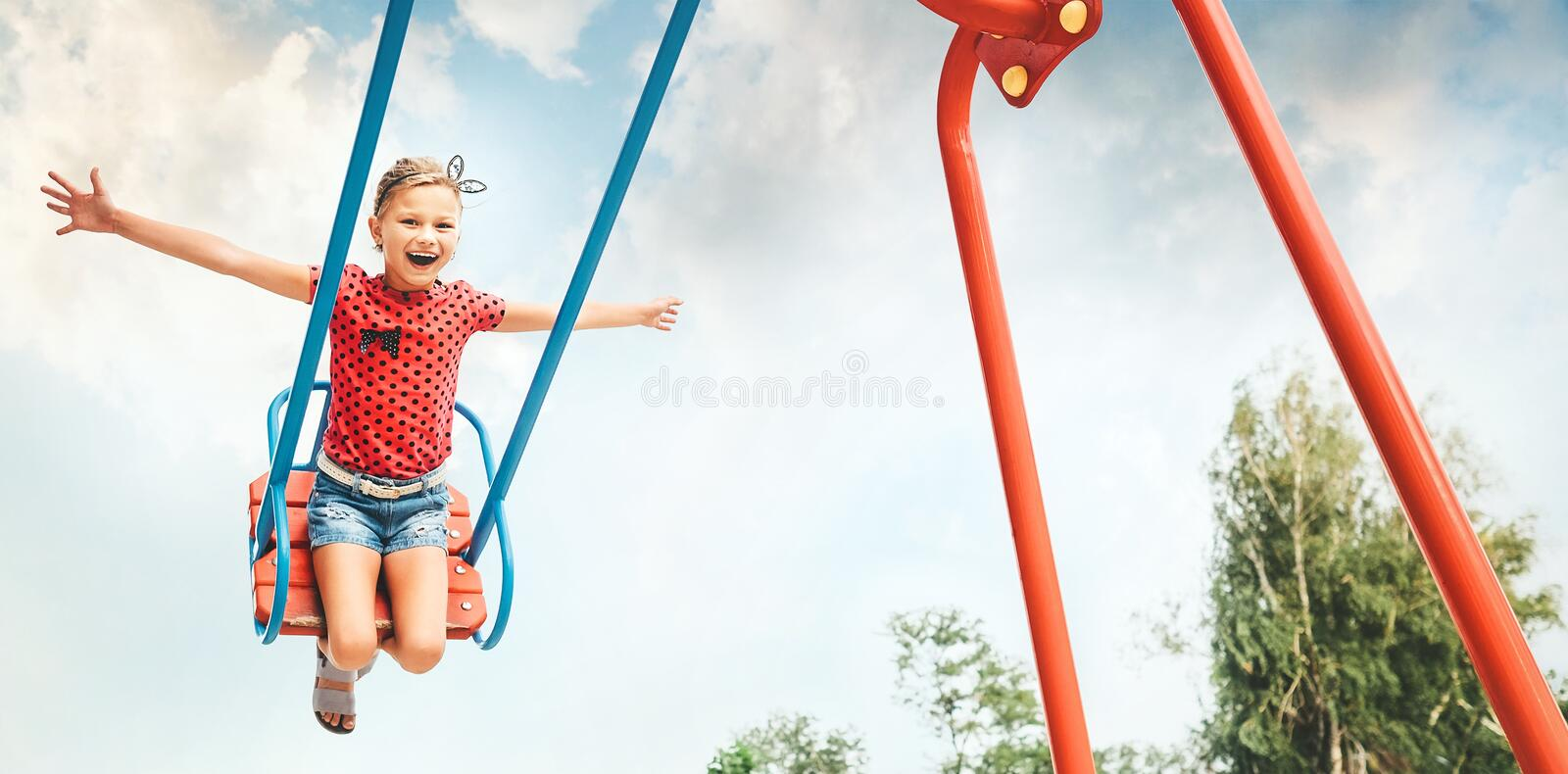 Happy little child girl laughing and swinging on a swing in the stock photo