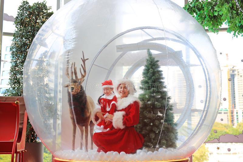 Happy little child girl and mother in santa costume dress has fun in big winter Snow globe with reindeer on christmas time. Merry. Xmas and happy new year stock photography