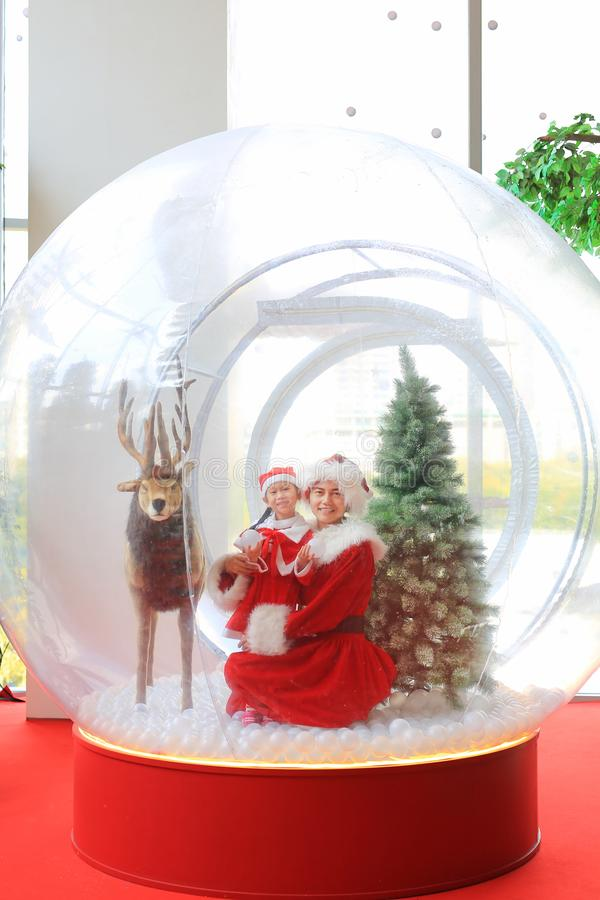 Happy little child girl and mother in santa costume dress has fun in big winter Snow globe with reindeer on christmas time. Merry. Xmas and happy new year royalty free stock photography